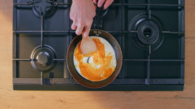 slo mo ld male hand mixing powdered turmeric with the cream in the pan - cooking pan stock videos & royalty-free footage