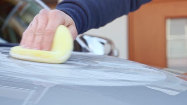 stockvideo's en b-roll-footage met mannenhand een spons in cirkelvormige bewegingen aanbrengen polijsten plakken op de kap van een zilveren auto verplaatsen - mouw