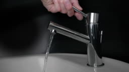 Male Hand Opening Faucet in a Bathroom