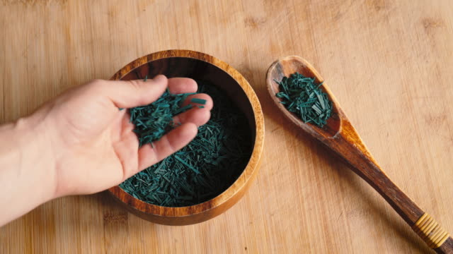 male hand picks up spirulina algae flakes - cianobatterio video stock e b–roll