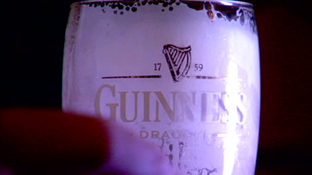 cu male hand placing empty guinness pint glass on wood surface glass coated on inside w/ draught beer foam english public house irish stout - empty glass stock videos and b-roll footage