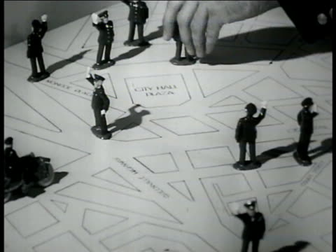 vídeos de stock, filmes e b-roll de male hand placing miniature police figures on street grid map adding police to traffic problem areas modeling traffic study results taking control - ornamento