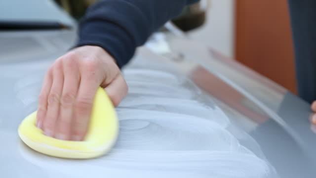 male hand placing polishing paste onto a silver car using a sponge - polishing stock videos & royalty-free footage