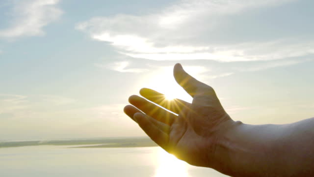 male hand play with sunset