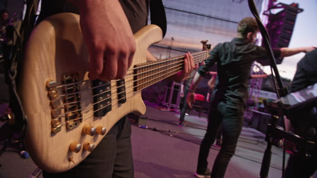 male hand playing electric guitar in concert - bass guitar stock videos & royalty-free footage