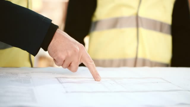 Male hand pointing to details on the construction plans on the table
