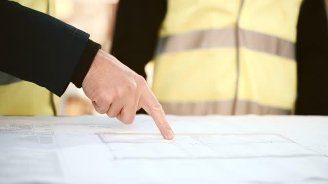 Männliche Hand Einzelheiten über die Pläne auf dem Tisch auf