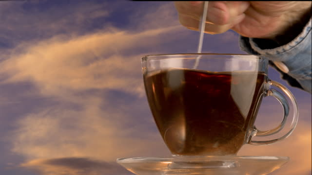 male hand pours hot tea into a glass cup and saucer - saucer stock videos & royalty-free footage
