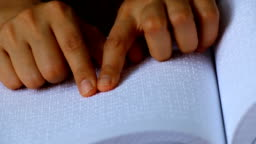 Male hand reading braille dot language for the Blind