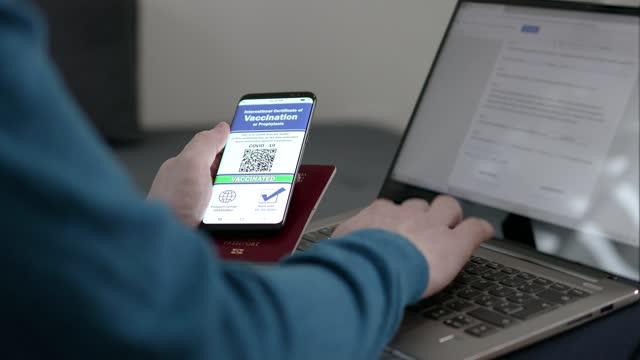 stockvideo's en b-roll-footage met mannelijke hand die internationaal vaccinatiecertificaat voor covid-19 codes van slimme telefoon aan laptop overtyping - document