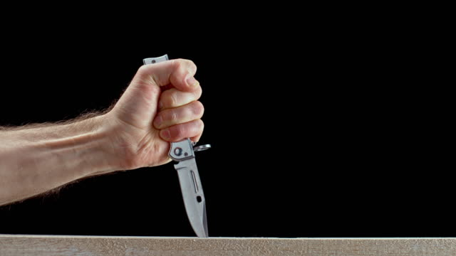 slo mo ld male hand stabbing a knife into the wood - knife crime stock videos & royalty-free footage