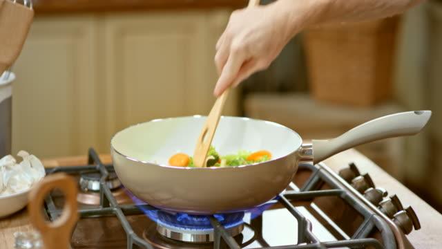 LD manlig hand omrörning grönsaker i en vit skål på gas spis