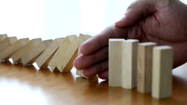 male hand stopping the domino effect. risk control concept - block shape stock videos & royalty-free footage