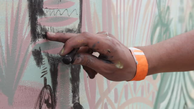 male hand uses charcoal to draw on wall - crayon stock videos and b-roll footage