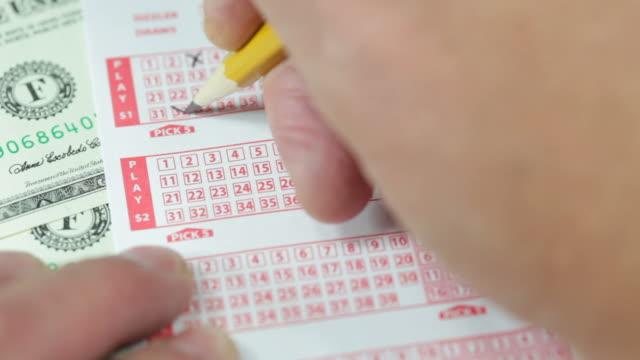 男性の手を使用してペンシルにマークロッタリー番号 - 宝くじ点の映像素材/bロール