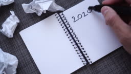 A male hand writes 2020 GOALS in a notebook on a gray textured table surface. Tears out the page and throws. Crumpled sheets of paper are nearby