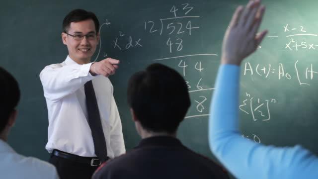 CU Male hand writing Chinese characters on blackboard / Singapore