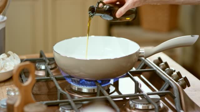 vídeos de stock, filmes e b-roll de ld macho mãos ajustando o calor do fogão e despejando azeite na panela de aquecimento - fogão