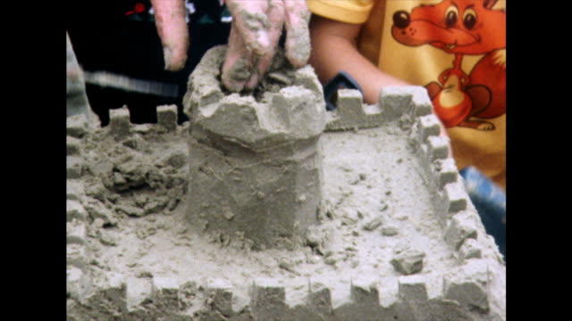 male hands creating sandcastle on beach; 1975 - family with two children stock videos & royalty-free footage
