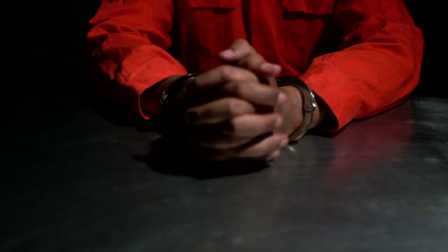 Male hands cuffed signing confession
