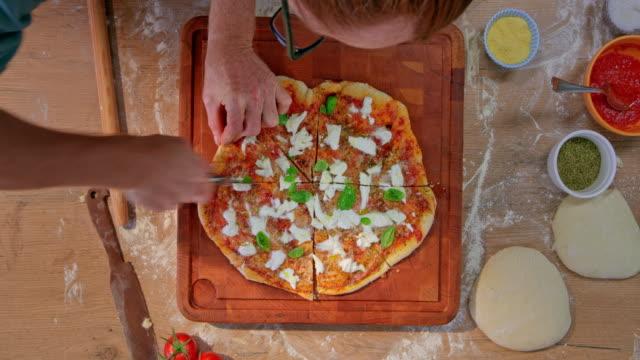 ld männliche hände schneiden pizza in scheiben - schneidebrett stock-videos und b-roll-filmmaterial
