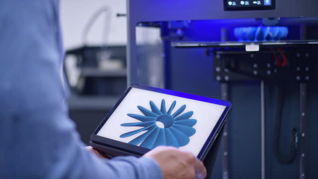 male hands holding a tablet with the design for a fan propeller while standing next to a 3d printer - image stock videos & royalty-free footage