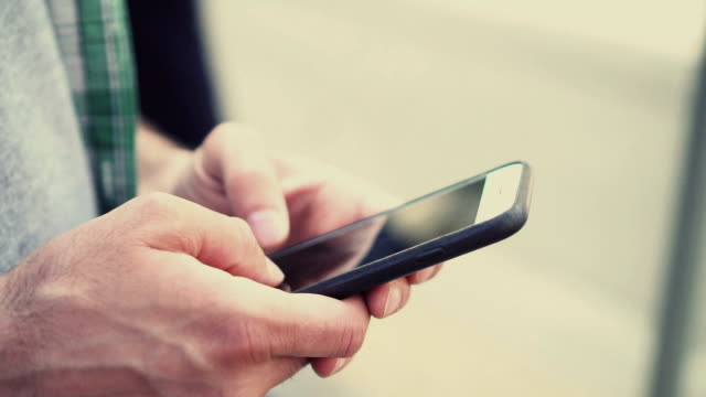 vídeos de stock e filmes b-roll de male hands holding cell phone and texting - ecrã tátil
