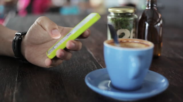 Male hands holding smartphone in coffee shop