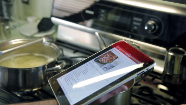 CU Male hands holding ipad and spaghetti sauce over stove, cooking recipe displayed on ipad / Santa Monica, CA, United States