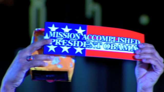 stockvideo's en b-roll-footage met male hands holding up mission accomplished president obama sign - 2008