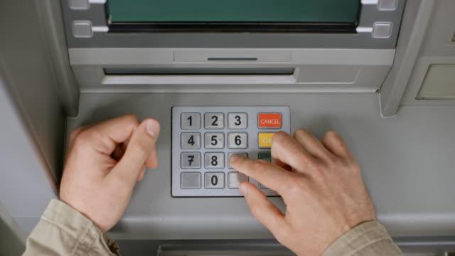 DS männliche Hände eine Bankkarte einlegen und Eingabe einer PIN-Nummer auf der ATM-Tastatur