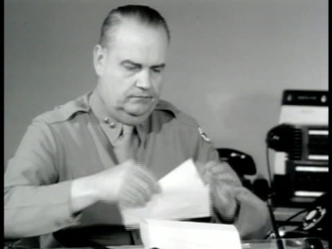 stockvideo's en b-roll-footage met reprisal male hands opening 'secret' letter on desk w/ opener ms us officer sitting at desk reading letter making telephone call another officer at... - 1943