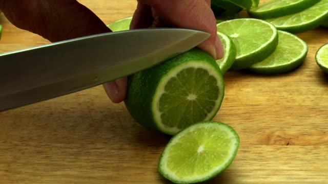 Male hands slice lime with sharp knife,