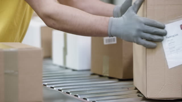 male hands sorting packages on the conveyor belt - glove video stock e b–roll