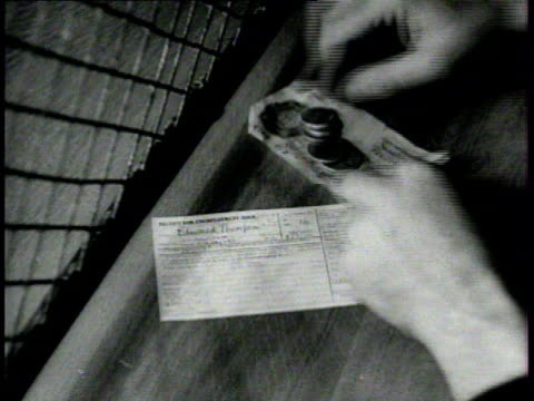 vidéos et rushes de male hands taking cash, paper money & coins, from female hands in cashier's cage window, unemployment, dole. male in suit, cigarette in mouth,... - hasard