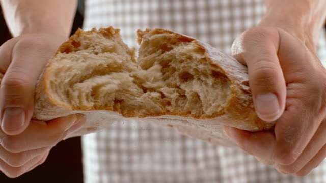 slo mo ld male hands tearing apart a loaf of bread - bread stock videos & royalty-free footage