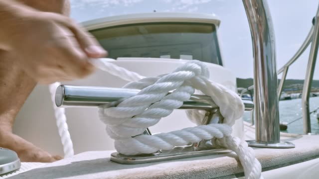 male hands tying a knot to the cleat on the boat - tied up stock videos & royalty-free footage