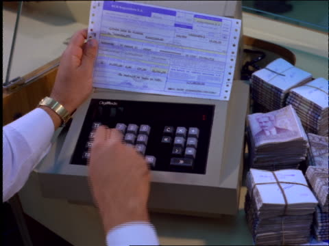 male hands typing on adding machine / banco bradesco / brazil - rechenmaschine stock-videos und b-roll-filmmaterial