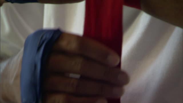 vídeos y material grabado en eventos de stock de male hands w/ blue wrappings, wrapping hands in red handwrap, wearing white tee shirt. - camiseta blanca