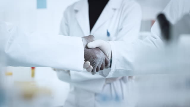 male handshake in the laboratory - epidemiology stock videos & royalty-free footage