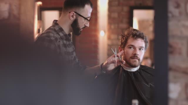 vídeos de stock, filmes e b-roll de male having haircut in barbershop - cabeleireiro