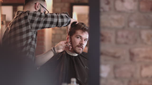 male having haircut in barbershop - barber stock videos and b-roll footage
