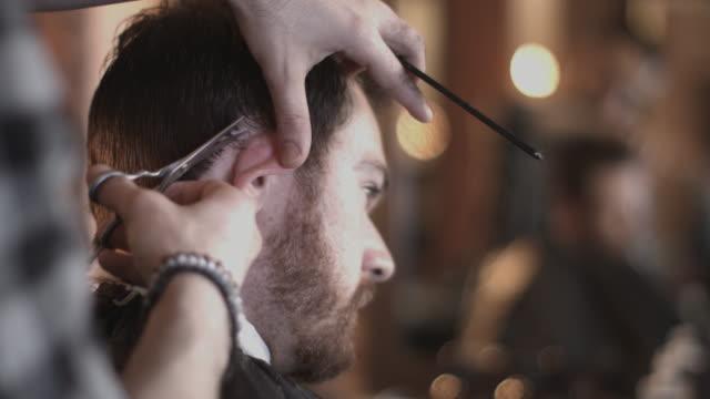 vídeos de stock, filmes e b-roll de male having haircut in barbershop - tesoura