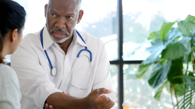 Male health professional discusses broken arm diagnosis with female patient