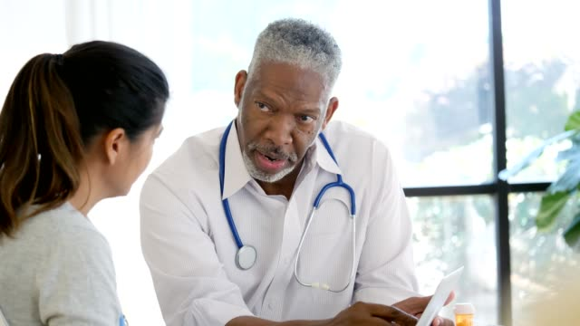male health professional explains an internet insurance application form to patient - patient stock videos & royalty-free footage