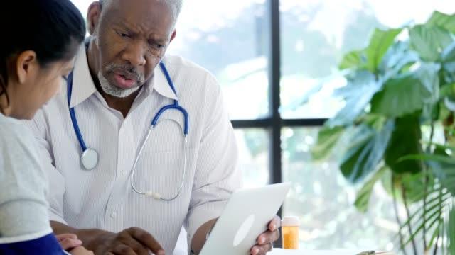 vídeos y material grabado en eventos de stock de hombre profesional de la salud explica aplicación de terapia física para paciente femenino - asistente sanitario