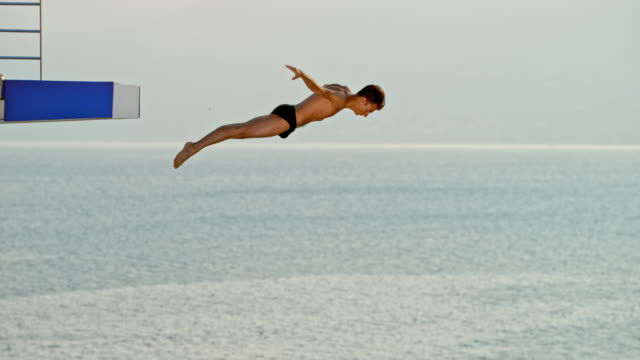 slo mo male high diver doing a jump at a competition in setting sun - scrittura occidentale video stock e b–roll