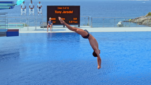slo mo male high diver taking off the board, rotating in the air and diving into the pool - concentration video stock e b–roll