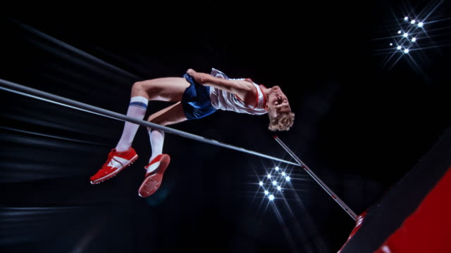 SLO MO Male high jumper jumping over the bar on black background with stadium reflector lights