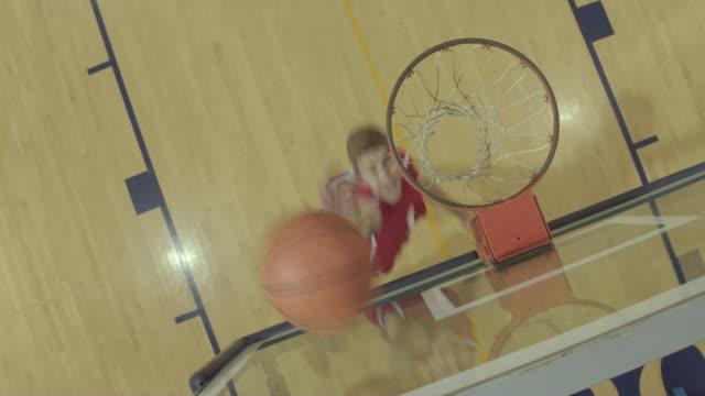 Jugador de baloncesto masculino preparatoria carreras para un layup en el aro